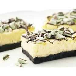 Chocolate Mint Cheesecake Bars Recipe - These festive minty cheesecake bars on top of a chocolate crumb crust are sure to be popular among your holiday guests. A drizzle of chocolate and mint candy pieces decorate them nicely.