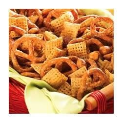 Nutty Snack Mix Recipe - Sweet, nutty breakfast cereal, mixed nuts, and pretzels are tossed in a peanut butter/cinnamon coating, baked and then dusted with cayenne for a sweet and spicy snack that's sure to please.