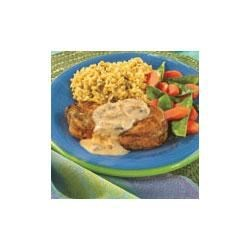 Herbed Pork Chops in Mushroom Sauce Recipe - Golden brown, seasoned pork chops simmer with onion in a creamy mushroom sauce and are served over hot cooked rice.