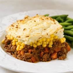 Classic Shepherd's Pie Recipe - A savory base of ground beef and vegetables in tangy tomato gravy and topped with a layer of buttery mashed potatoes. It's the perfect comfort food for your hungry family.