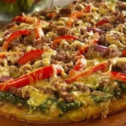 Smoked Sausage Pizza Recipe - This delicious pizza has a hint of sweet and smoke from peach preserves and smoked Gouda. With a pesto sauce and crumbled Italian sausage, it's sure to be a new family favorite.