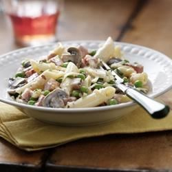 Penne with Ham, Mushrooms and Peas Recipe - Pasta perfectly balanced with diced ham, slices of mushrooms and fresh garden peas in a delicate creamy sauce, finished with a touch of fresh lemon juice and smoked Cheddar.