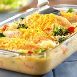 Cheesy Chicken and Rice Recipe - Cheddar cheese is melted over pan-fried chicken breasts and served over creamy rice in this showpiece meal.