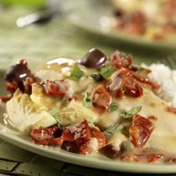 Chicken in Creamy Sun-Dried Tomato Sauce Recipe - Mediterranean flavors such as sun-dried tomatoes, kalamata olives, capers, artichoke hearts, tomatoes and white wine simmer together to flavor chicken breasts in this mouthwatering slow-cooker dish.