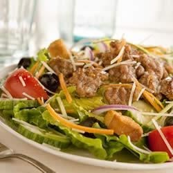 Summertime Sausage Salad Recipe - Bring the freshness of your vegetable garden inside for a green salad loaded with color and crunch; then top it off with cooked, crumbled Italian sausage for a complete meal.