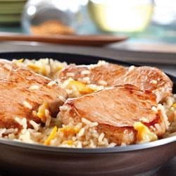 Quick Glazed Pork and Rice Skillet Recipe - This speedy skillet dish features browned boneless pork chops and rice simmered in a sweet and sour sauce made with Swanson(R) Chicken Stock, Dijon-style mustard and apricot preserves.