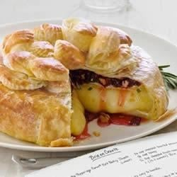 Dried Cherries, Pecans and Rosemary Brie en Croute Recipe - Dried cherries, toasted pecans, and honey top this brie round baked in puff pastry.