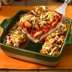 1-Dish Chicken Parmesan Recipe - Ready to serve in less than an hour, this one-dish meal layers chicken, marinara sauce and shredded cheese on a yeast bread base for the best flavors of Italy.