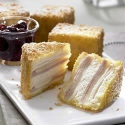 Monte Cristo Sandwich Recipe - Slices of ham, turkey, and Swiss cheese are layered between soft slices of bread, then deep fried with a crispy crust of panko bread crumbs in this updated version of a classic hot sandwich.