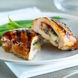 Brie and Sage Stuffed Chicken Recipe - Creamy Brie cheese and salty prosciutto transform ordinary grilled chicken breasts into an indulgent, company-worthy dish. For entertaining ease, stuff the chickens up to one day in advance; reserve in the refrigerator until 30 minutes before grilling.