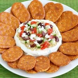 Greek Garden Spread Recipe - A cream cheese and yogurt layer is spread with hummus then topped with chopped cucumber, tomato, crumbled feta cheese, and olives in this Greek-inspired cracker spread.