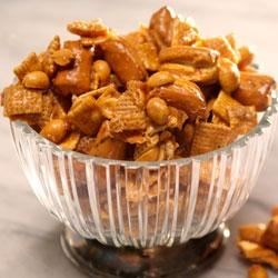 Crunchy Caramel Snack Mix Recipe - Bake crunchy cereal, pretzels, melted caramel, and peanuts together for a sweet and savory snack treat.