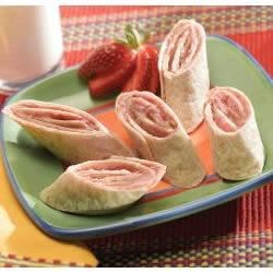 Peanut Butter and Jelly Roll-Ups Recipe - Peanut butter, strawberry preserves, and cream cheese come together in this kid-pleasing tortilla roll-up.