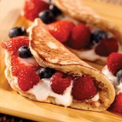 Banana Berry Pancakes Recipe - Banana-nut pancakes are topped with yogurt and sliced berries then folded in half for a special breakfast or brunch treat.