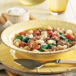 Sausage and Bean Ragout Recipe - This hearty and colorful stew packed with sausage, onion, tomatoes, beans, pasta, spinach leaves and Romano cheese is sure to satisfy even the hungriest family member.