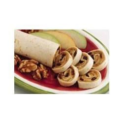 After School Fruit Rolls Recipe - In this twist on the classic peanut butter and banana sandwich, peanut butter is spread on flour tortillas, and then wrapped around a cinnamon and honey-sweetened mixture of bananas and raisins.