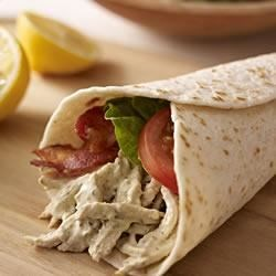 Pesto-Chicken Club Wrap Recipe - Shredded chicken in a creamy pesto sauce stars in these easy tortilla wraps with bacon, tomatoes, and lettuce.