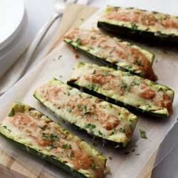 Grilled Stuffed Zucchini Boats Recipe - Scooped-out zucchini 'boats' are grilled with a creamy tomato-basil sauce and shredded cheese, and topped with parsley for a great summer barbecue side dish.