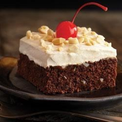 Caramel Brownie Cake Recipe - Rich, chocolate brownies with two toppings--caramel and creamy--are served with a bright red cherry on top.
