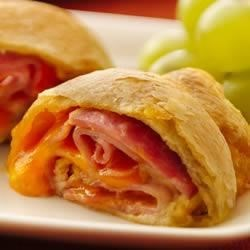 Ham and Cheese Crescent Roll-Ups Recipe - Ham and cheese crescents add an easy wow to a weeknight dinner, ready in just 25 minutes.
