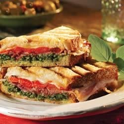 Prosciutto and Provolone Panini Sandwiches Recipe - The perfect flavor combo--prosciutto, Provolone, pesto, and roasted bell peppers--on rustic bread and toasted in a panini press makes a great lunch or a quick, light dinner.