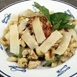 Chicken Pesto a la Lisa Recipe - The sunny, nutty taste of basil and pine nuts melds with the rich notes of sun-dried tomatoes in a chicken sauce flavored with garlic and a handful of feta cheese. Serve over hot pasta and top with a grating of Parmesan cheese.