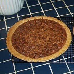 Milk Chocolate Pecan Pie Recipe - A sweet, butter and egg mixture is combined with lots of pecans and milk chocolate pieces, spooned into a prepared pie crust and baked. The chocolate melts, the pecans get gooey, and the crust turns golden brown.