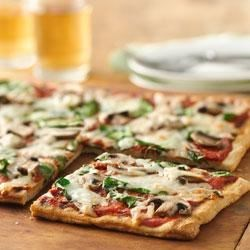 Mushroom-Pesto Grilled Pizza Recipe - The secret to perfect grilled pizza is to grill the crust first, then add the toppings. Serve one slice as an appetizer or two with a salad for a simple supper.