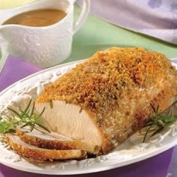 Dijon-Herb Pork Roast Recipe - An herb-studded pork roast wears a coat of crunchy bread crumbs and a sweet and tangy mustard and currant jelly sauce.