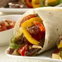 Sizzling Steak Fajitas Recipe - Tex-Mex perfection for everyone--Fajitas are fun for everyone. Enjoy this Tex-Mex recipe at home--throw a fajita party where your friends and family build their own fajitas and make memories that last. Our fajitas recipe relies on GOYA(R) Mojo Criollo as a flavorful marinade that delivers juicy, tender meat, and GOYA(R) Flour Tortillas for a pocket everyone can pick up.