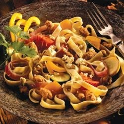 Fettuccine with Roasted Tomatoes, Vegetables and Sausage Recipe - This easy, light supper dish is made with fettuccine pasta, mild Italian sausage, and colorful plum tomatoes, zucchini, and sweet yellow peppers. Feta cheese adds a final savory touch.