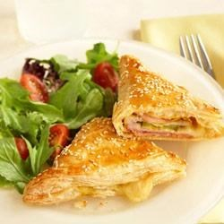 Cuban-Style Turnovers Recipe - What makes these puff pastry turnovers Cuban? It's the tasty combination of ham, cheese and pork seasoned with mustard and pickles. Give these a try...they're really good.