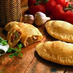Sausage and Mushroom Calzones Recipe - A quick and easy family meal, these calzones are filled with sausage and mushrooms.