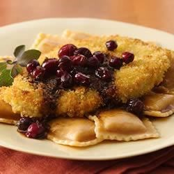 Turkey Scallopini and Squash Ravioli with Cranberry Brown Butter Recipe - Thin pieces of turkey breast are breaded and browned, then served over squash ravioli and topped with a rich sage-cranberry sauce.
