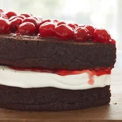 Decadent Chocolate Cherry Torte Recipe - Chocolate cake, juicy cherry filling, and whipped cream are topped with crunch almond slivers.