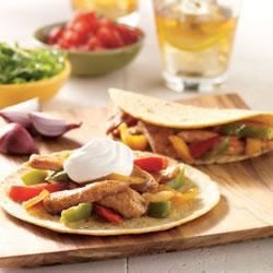 Soft-Shell Chicken Tacos Recipe - Serve up spicy chicken tacos with veggies and sour cream in just 15 minutes.
