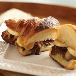 Banana Hazelnut Breakfast Panini Recipe - Breakfast never tasted so good--buttery croissants spread with chocolate hazelnut, topped with crispy bacon, banana slices, and cinnamon sugar are baked until golden brown.