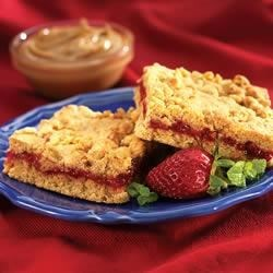 Peanut Butter and Jelly Oat Bars Recipe - Topped with strawberry preserves, these peanut butter flavored treats are any-time-of-day snacks.