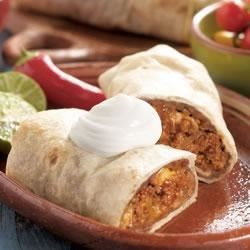 Traditional Beef Burritos Recipe - Dinner's on the table in less than an hour with these delicious bean and beef burritos, baked and browned, and topped with a dollop of sour cream.