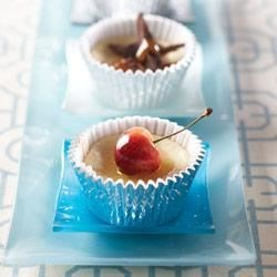 Individual Vanilla Cheesecakes Recipe - Cupcake-sized cheesecakes make pretty, little desserts decorated with fresh fruit, jam, or chocolate curls.