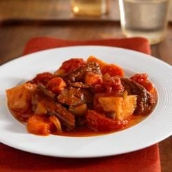 Slow-Cooked Pot Roast Recipe - Tender pot roast with red potatoes and carrots in a savory tomato sauce.