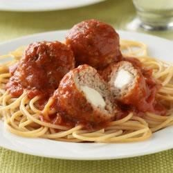 Mozzarella-Stuffed Meatballs Recipe - Ground turkey meatballs served with spaghetti and sauce will be a hit with the entire family when they discover the hidden pocket of cheese inside the meatballs.