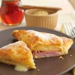 Baked Monte Cristo Sandwiches Recipe - Set aside the bread and serve this ham and cheese melt on puff pastry instead. Sweet and savory never tasted so good...especially when topped with a sprinkle of confectioners' sugar.
