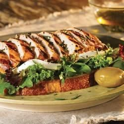 Open-Faced Grilled Tuscan Chicken Sandwiches with Fresh Mozzarella Recipe - Marinated, grilled chicken with rosemary is served on slices of grilled rustic bread with baby greens and fresh mozzarella cheese.