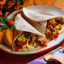 Maple Sausage Breakfast Burritos Recipe - Eggs and maple sausage are rolled up with peppers, green onions, salsa, cream cheese, and Monterey Jack -- for a breakfast burrito that will get everyone scrambling out of bed!