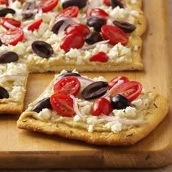 Greek Salad Pizza Recipe - This tasty pizza is made with all of the best flavors of Greece on top of an easy roll-out crust.