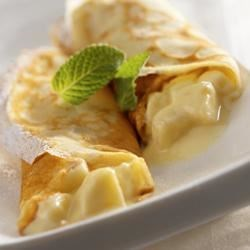 Banana and Yogurt Crepes Recipe - Thin and elegant crepes filled with a smooth, pureed nutrient-rich, low-fat yogurt, vanilla and honey mixture, and fresh sliced bananas. Yogurt contains lactose, but its live and active cultures help with digestion, making this recipe a friendly option for those who are lactose intolerant.