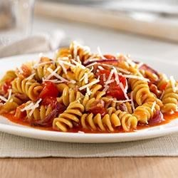 Rotini with Cherry Tomatoes, Caramelized Onions and Pancetta Recipe - Colorful and delicious, this pasta dish uses a crowd-pleasing combinations of fresh tomatoes, crisp pancetta and Barilla Veggie Rotini, made with spinach and zucchini for an extra boost of veggies.