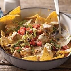 Quick-Fix Chicken Enchilada Skillet Recipe - Spicy chunks of chicken and kidney beans in a creamy sauce are topped with shredded lettuce, pico de gallo, and shredded Cheddar cheese and served up with crunchy tortilla chips.