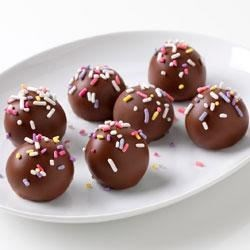 Banana Cake Balls Recipe - These chocolate-coated banana cake balls are fun and easy to make. Decorate them with multi-colored sprinkles for a festive dessert.